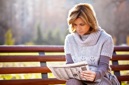 Beautiful woman is reading a newspaper in the park.